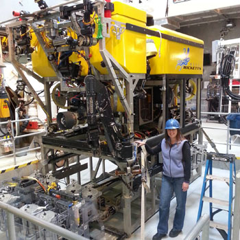 Research Assistant Kristine Walz stands next to ROV Doc Ricketts, which reaches well above 10 feet tall on top of the midwater tool sled.
