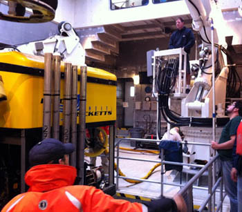 First Mate Erik Larson (top right) pays out the line that lifts the ROV after the recovery as Eric Martin (far right) and Ben Erwin look on.