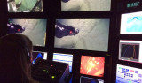 """Katie Coble from the US Geological Survey controls the science camera on ROV Doc Ricketts from the Western Flyer control room. The video screens show the ROV manipulator collecting a """"push core"""" to from layers of sediment in Monterey Canyon, 1,600 meters below the ocean surface."""