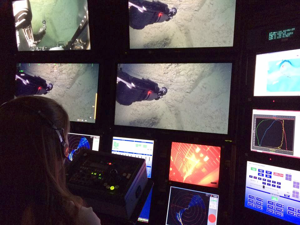 "Katie Coble from the US Geological Survey controls the science camera on ROV Doc Ricketts from the Western Flyer control room. The video screens show the ROV manipulator collecting a ""push core"" to from layers of sediment in Monterey Canyon, 1,600 meters below the ocean surface."