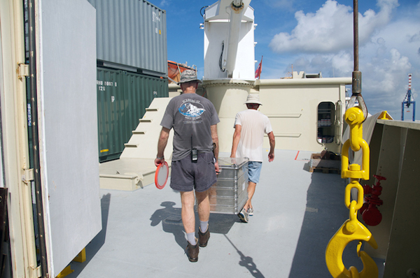Chief scientist Ken Smith and engineer Fred Uhlman carry a box of equipment to the science lab. The main activities for the research team during the port stay are unloading equipment and preparing the working areas. The science areas of the ship are like an empty office space that has to be moved into. Sample jars and equipment get organized in the science lab; computers and printers are connected to the ship network; materials are checked and rechecked as this is the last opportunity to replace a broken or missing part. Everything also must be secured so that it doesn't get damaged with the movement of the ship at sea.