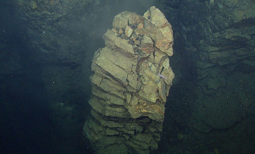 A column of magma intruded into the crust and cooled slowly after it was emplaced. It has been exposed and peeled away from the wall through subsequent tectonic rifting and erosion.