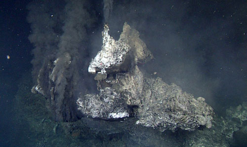 A sulfide flange sticks out toward the ROV at the top of an 18-meter-high black smoker in the newly discovered vent field at Alarcón Rise. Hot vent fluids are exiting the structure underneath this flange (as well as from a more classic chimney orifice at the top), ponding underneath,