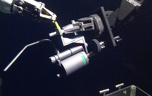 A sampler for collecting hot hydrothermal vent fluids is transferred from one manipulator arm's grip to the other prior to sampling. The nozzle on the left will be inserted into the black smoker's orifice. The trigger to draw in the sample is the hydraulic ram with the black circular plate attached below the manipulator's