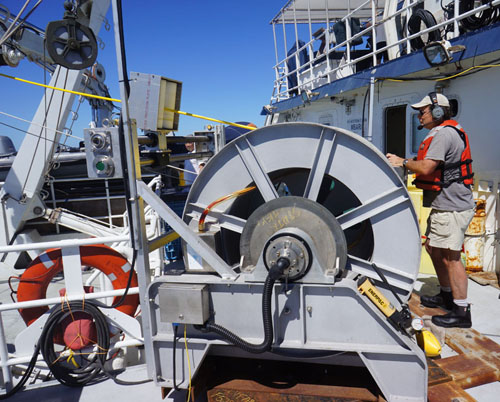Kim Reisenbichler operates the MiniROV's tether winch during the recovery.