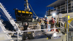 Although the mini ROV is much smaller than the Doc Ricketts, launching it still involves a coordinated effort with someone at the crane and the tether winch as well as the captain on the bridge working in unison, to ensure a safe deployment.