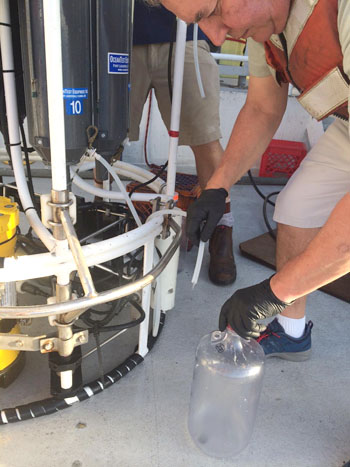 Francisco Chavez collects seawater samples from the Niskin bottles mounted on the CTD rosette.