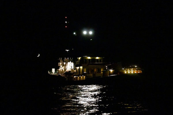 A waxing crescent moon shines on Lone Ranger as seen from the small tender boat at night.