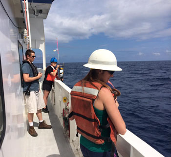 From left, Second Mate Trevor Daviscourt, Gabriela Chavez, and Monique Messié assist in deploying the sediment trap and buoy.
