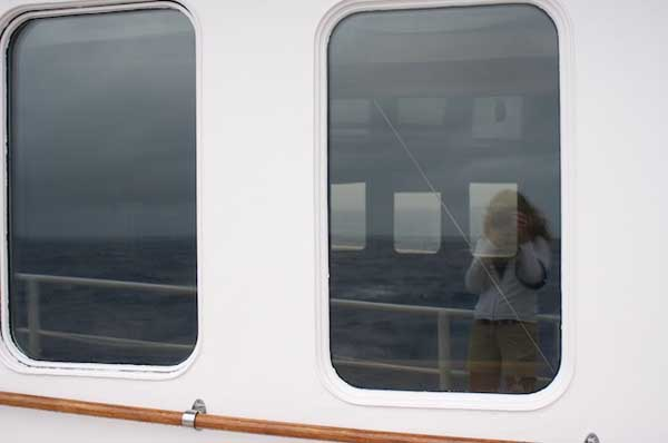 It's difficult to capture the rolling swells and winds in a photograph, but I have been trying. We've had numerous rain squalls today and the winds have increased to 20 knots. The port side windows in this image created a reflection of my efforts and also a view to the starboard side of the ship.