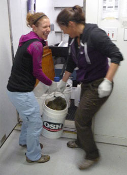 "Ph.D. Student Alexis Pasulka (left) and Professor Victoria Orphan (right) carry the large rock into the cold room. I asked, ""Didn't you notice how big it was in the video?"" to which she replied ""Go big or go home"". I think that sums it up nicely."