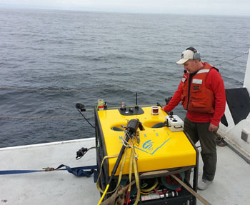 Dale Graves, the lead engineer of the MiniROV project, prepares for the first dive of the expedition.