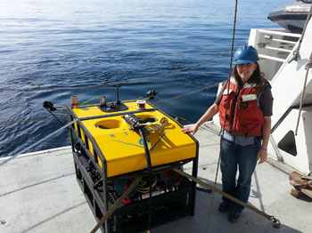 Kristine Walz next to the MiniROV, which stands just a few feet tall, but can be used as a fly-away vehicle in remote locations.
