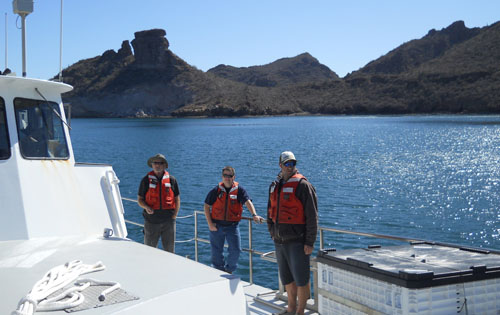 Perry Shoemake, Jim Boedecker, and Paul Ban stand on deck as the Zephyr nears port in San Carlos on the mainland of Mexico near Guaymas.