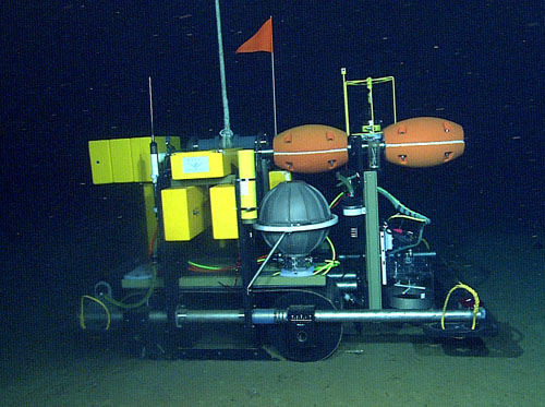 The Benthic Rover is a mobile physiology lab. In a series of experiments, the rover measures how much oxygen seafloor organisms use. The rover is about the size of a riding lawnmower. It drives across the soft seafloor on caterpillar treads, which distribute the rover's weight, have a better grip, and make less impact on the bottom than wheels. Although the rover weighs more than a ton in air, buoyant foam panels reduce that to 45 kilograms (100 pounds) in water.