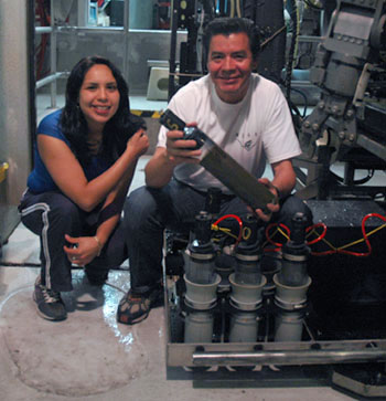 Gabriela Cervantes and Martín Hernández Ayón with one of the push-core sediment samplers they took off the remotely operated vehicle. The two have had a few such mud samples to process every night; they carefully separate out sections of the core for later testing for trace metals.