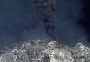 Hot, mineral rich water spews from a hydrothermal vent on the seafloor. Also known as black smoker, the mineral rich water appears as a column of black smoke rising from the seafloor. White, floculent bacterial mat is seen on the surface of the chimney below the black smoker.