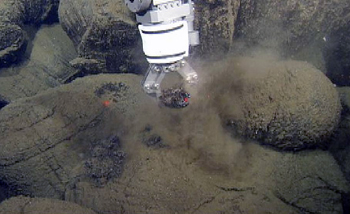 The ROV's manipulator arm takes a sample from a pillow lava.