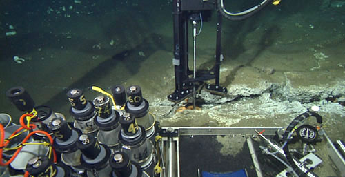 This view from the main camera on the remotely operated vehicle gives an idea of the various sampling tools carried to the seafloor to conduct chemistry studies. The laser Raman probe in a specially designed tripod with a hydraulic actuator sits above a fissure lined with white and orange bacteria. In the foreground, from left are the thermistor at the end of the orange cable, used to measure the temperature of venting fluids; push core tubes used to collect mud from the seafloor; and the pump and gauges used for the precise operation of the Raman spectrometer.