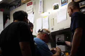 Knute, Eric, Bryan, and Matt Noyes fixing a part for the ROV.