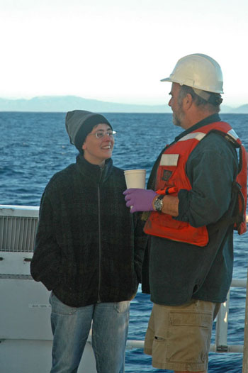 Carmen Castro and Tim Pennington chat on the aft deck while waiting for the CTD to resurface this morning. The coast of Baja California lies on the horizon.