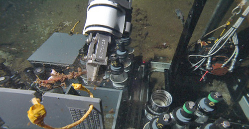 The remotely operated vehicle (ROV) has many types of samplers on its toolsled to carry samples to the surface for scientists to study onboard the ship. In the upper right is the vibracore system; the two gray boxes are for rocks or large biology samples such as clams; and the suite of small numbered tubes (lower right) are push cores for sampling sediment in different areas of the canyon. The manipulator arm is putting a small piece of wood in the sampling box.
