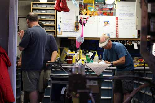 Pinky the Easter bunny watches over the ROV shop while Knute fixes a part for the ROV.