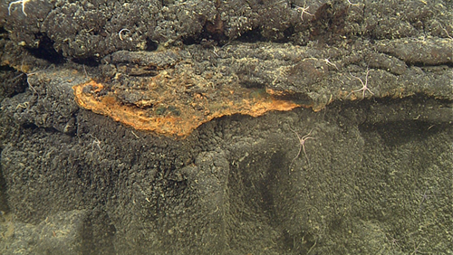 layers of orange hardened sediment cap underlying lavas