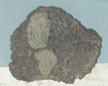 Lava (brown) containing olivine-rich xenoliths (greenish) collected offshore of Kauai. Photo © MBARI 2001
