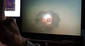 During the Coordinated Canyon Experiment in October 2015, MBARI researchers used the remotely operated vehicle Ventana to dig a four small pits in the floor of Monterey Canyon and then placed benthic event detectors in the pits. This photograph shows a video screen in the ROV control room just after a BED was deployed in the canyon. Image: Krystle Anderson © 2015 MBARI.