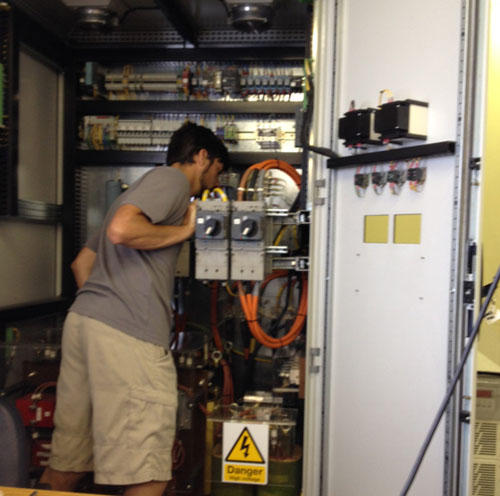 ROV pilot Bryan Schaefer inspects inside the ROV Doc Ricketts' power distribution unit (PDU) in the ship's dry lab.