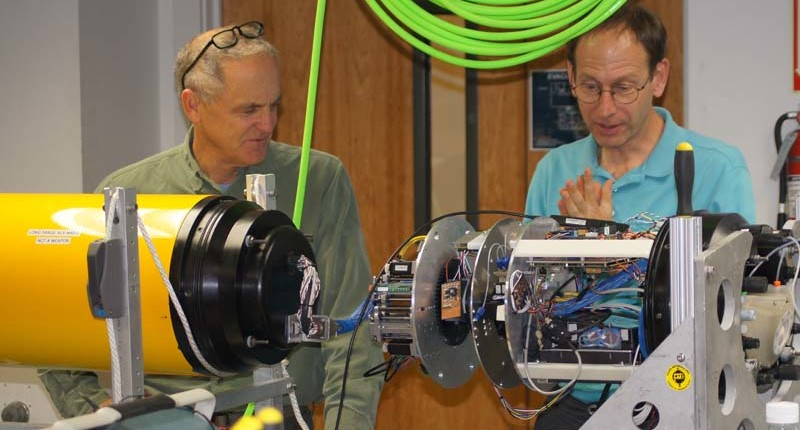 Engineers Brett Hobson and Brent Roman discuss the joining of the third-generation Environmental Sample Processor to the front of the long-range autonomous underwater vehicle.