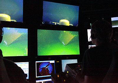 Scientists in the ROV control room on board MBARI's research vessel Western Flyer watch as the ROV Doc Ricketts approaches the sunken shipping container. Image: Chad King, Monterey Bay National Marine Sanctuary