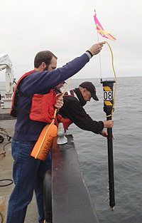 Project manager John Ryan and Rachel Carson crew member Vincent Nunes launch a drifter off the side of the research vessel Rachel Carson. Image: Eric Martin