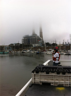 Second mate Miriam Anthony keeps watch on the back deck as the Western Flyer pulls out of from its slip in the harbor. The fog partly obscures the Moss Landing power plant's stacks in the background.