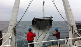 Meghan and Alex deploying the midwater trawl net from the stern of the RV Western Flyer.