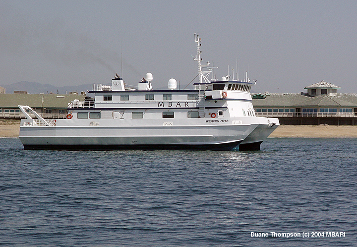 The research vessel Western Flyer steaming past the main building of the Monterey Bay Aquarium Research Institute in Moss Landing, California.
