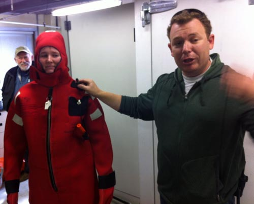 Kat Bolstad looking on (in her immersion suit) as Andrew McKee explains all the safety features.