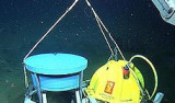 This photo shows the robotic arm on MBARI's remotely operated vehicle (ROV) Ventana lowering the DEIMOS instrument onto the seafloor. The blue cylinder works like a fish finder, sending sound waves up from the seafloor to detect fish and other animals swimming above. Image: (c) 2009 MBARI