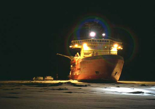The RVIB Palmer broke through ice to deliver supplies to a research station. Note the trucks parked on the ice next to the starboard side of the ship. Photo by Mike Watson.