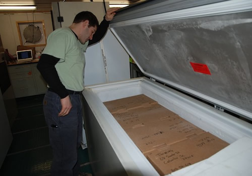 Ben Twining checks the boxes of frozen samples that will be shipped in special temperature-controlled boxes back to the University of South Carolina. Photo by Debbie Nail Meyer.