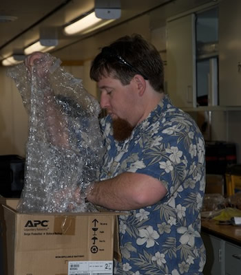 Jake Ellena packs a box for shipping back to MBARI. Photo by Debbie Nail Meyer.