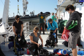 The blue-water divers assemble their gear on the back deck. The ship's crew prepares the small boat for launch.
