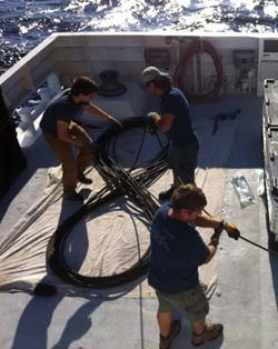 Ben Erwin, Mark Talkovic, and Randy Prickett coil 300 meters (985 feet) of damaged tether on the back deck.
