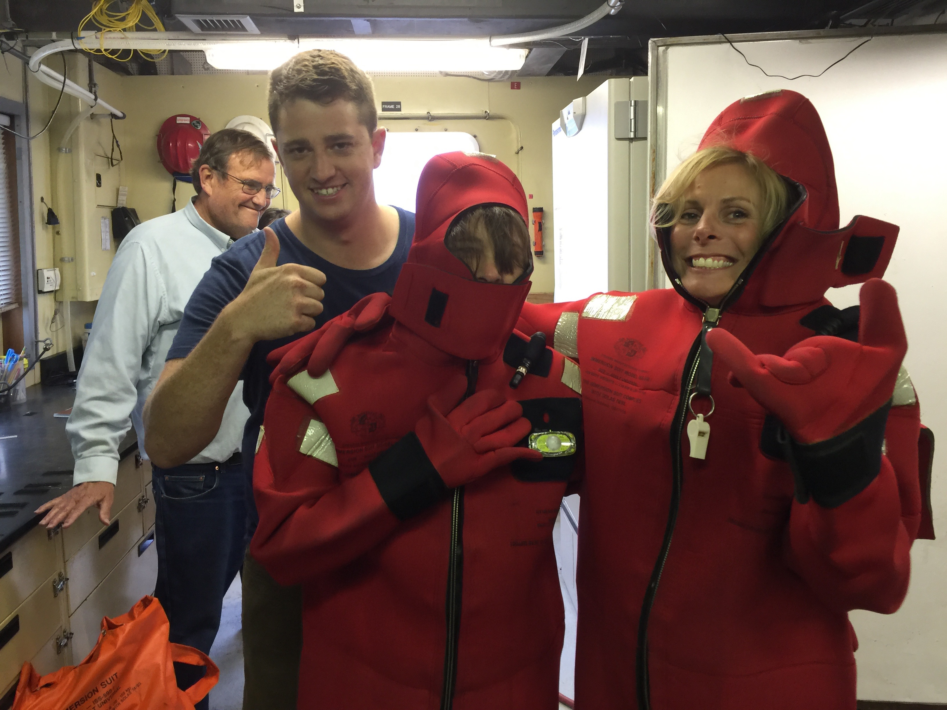 Second Mate Trevor giving Kris Walz and Shannon Johnson tips on how to get their immersion suits fully zipped up during our safety briefing. Jim McClain is photobombing behind them.