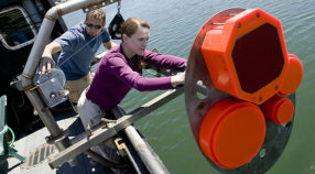Kelly Benoit-Bird and Chad Waluk work on a sonar transducer system.