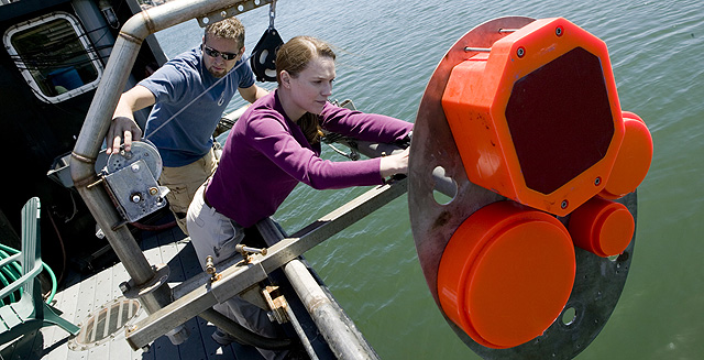 Kelly Benoit-Bird and Chad Waluk work on a sonar transducer system.