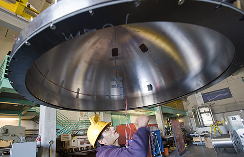 Scott Jensen inspected the upper half of the ESP's titanium pressure housing before it was assembled. The surfaces where the two half-spheres meet must be perfectly clean and smooth to prevent leaks. Image: Todd Walsh © 2009 MBARI