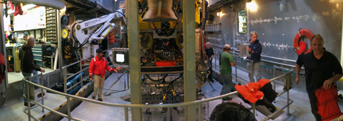 Panorama of the moonpool after the ROV recovery. Crew, pilots, and scientists are all busy when the ROV comes on deck. Pilots secure the ROV and then, with the help of crew, prepare the tether for the next deployment while the science team unloads samples.