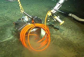 This photo shows the titanium pressure housing for the MOBB seismometer being lowered into a protective casing in the seafloor. This ultra-sensitive instrument was first installed in Monterey Bay in 2002. The seismometer operated on batteries (which had to be changed every three months) until it was hooked up to the MARS observatory in early 2009. Image: (c) 2002 MBARI